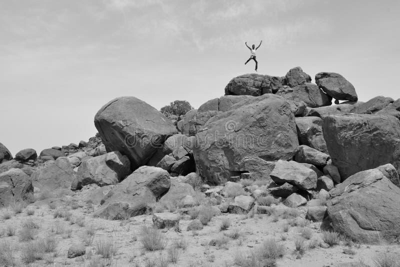 Man jumping on a pile of rocks in the desert -B&W-. Man jumping or fighting on a pile of rocks in the desert royalty free stock photo