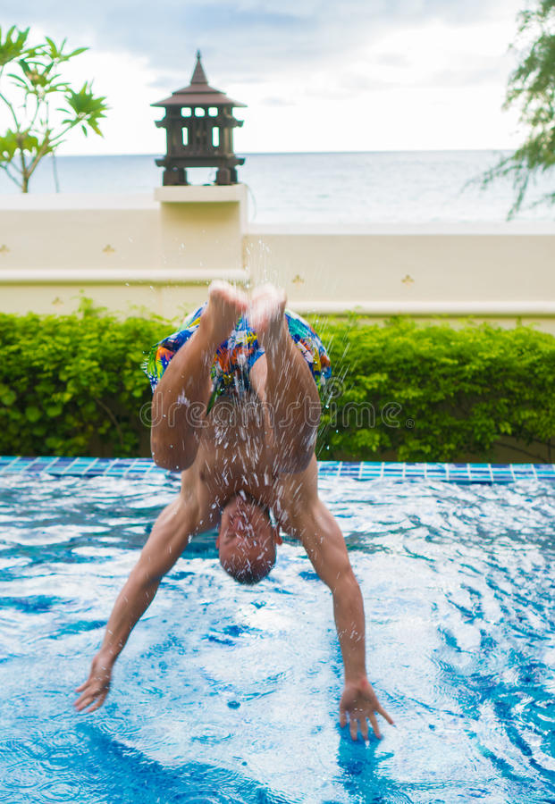 Man jumping into the pool stock image