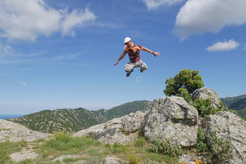 Man jumping from rock and flying in blue sky with beautiful mountain background. Extreme hiking stock photography