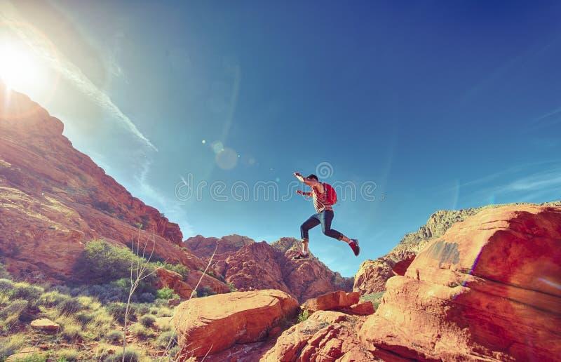 Man jumping on rocks in desert royalty free stock photo