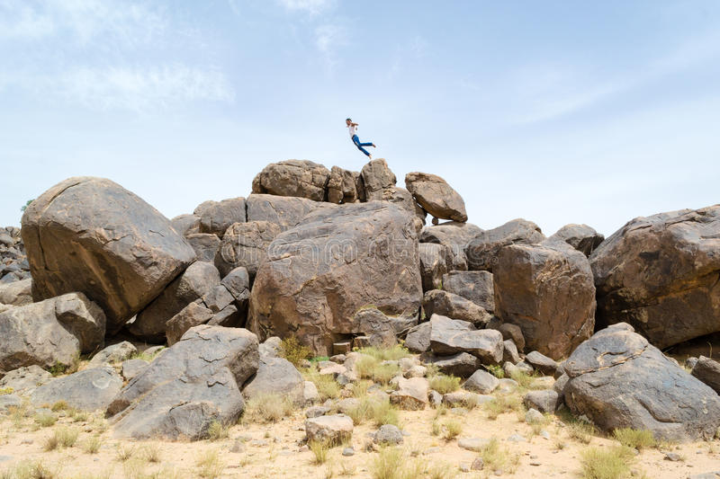 Man jumping on rocks in the desert #3. Man jumping high in the sky on top of a pile of desert rocks royalty free stock photos