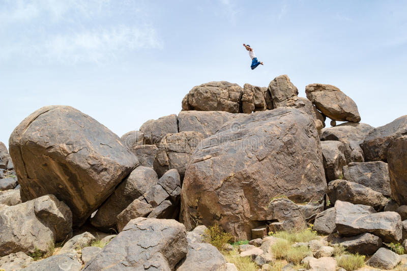 Man jumping on rocks in the desert #1. Man jumping high in the sky on top of a pile of desert rocks royalty free stock photo