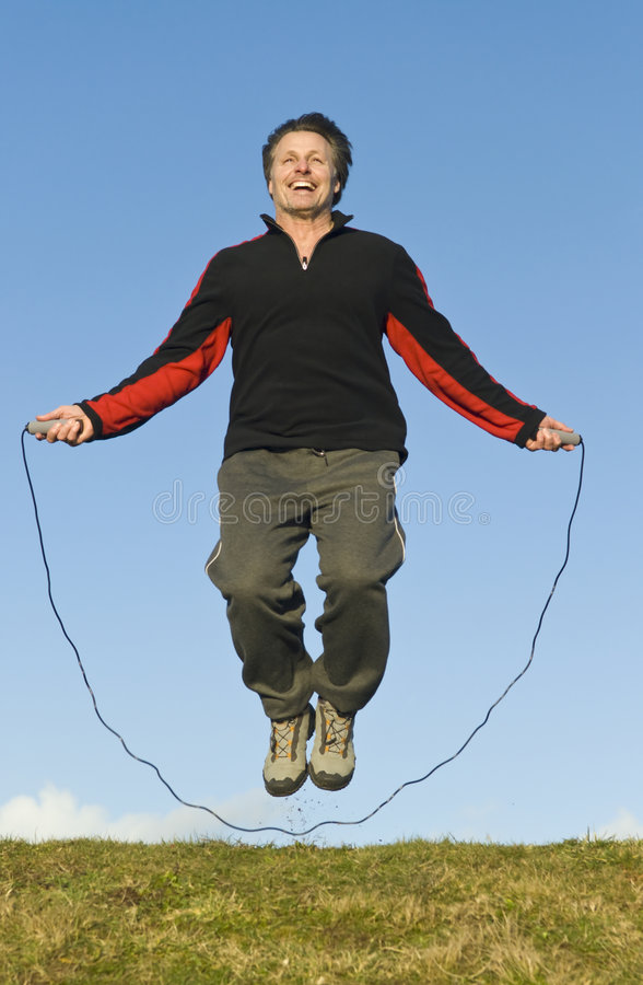Man jumping rope. A forties man is doing some skipping on the grass outdoors against a backdrop of a blue cloudy sky stock photo