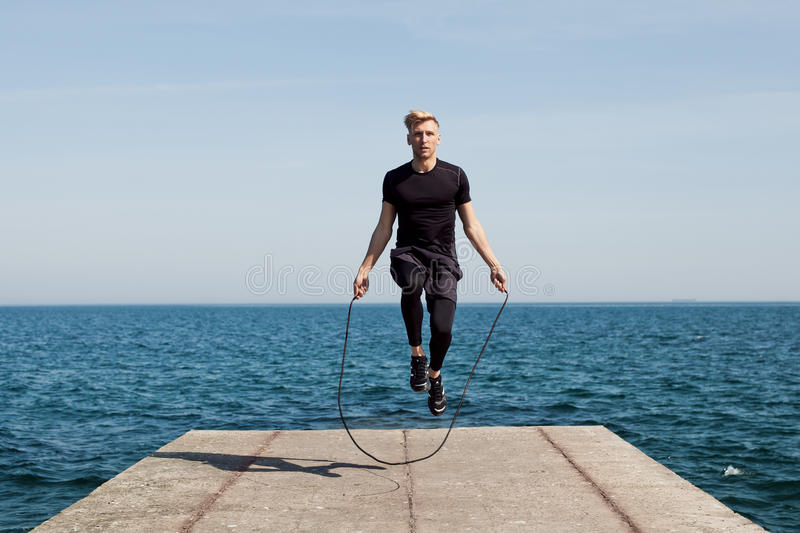 Man with jumping rope on pier stock image