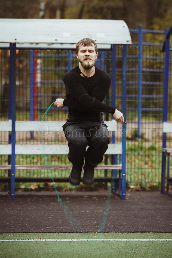 Man jumping with skipping rope. Healthy athlete jumping with skipping rope outdoor stock photo