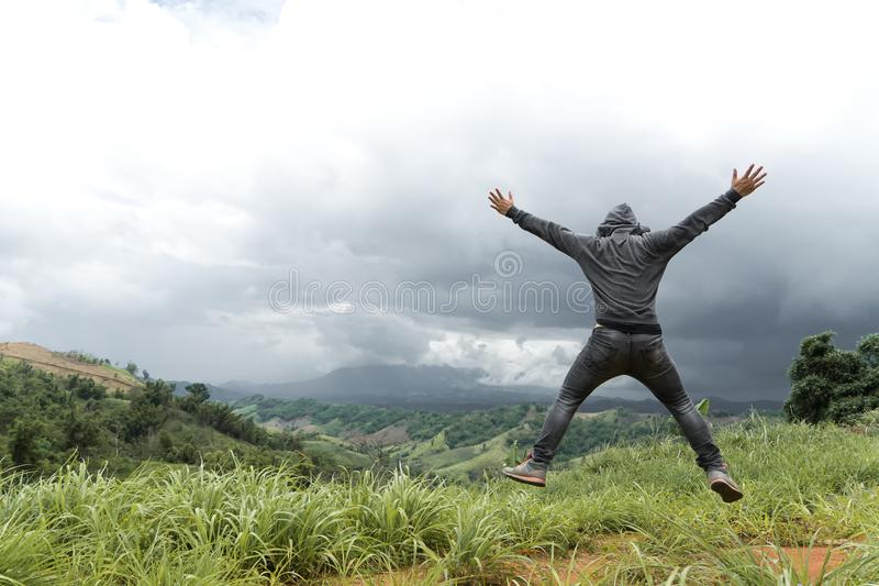 Man jumping on top of mountain hill, Freedom climber on high valley outdoor landscape. stock image