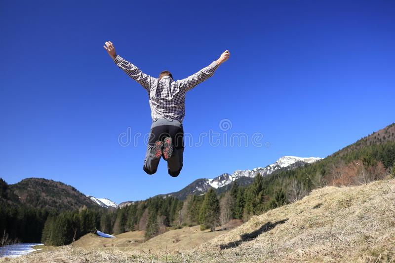 Man is jumping up the air. On a sunny day royalty free stock photo