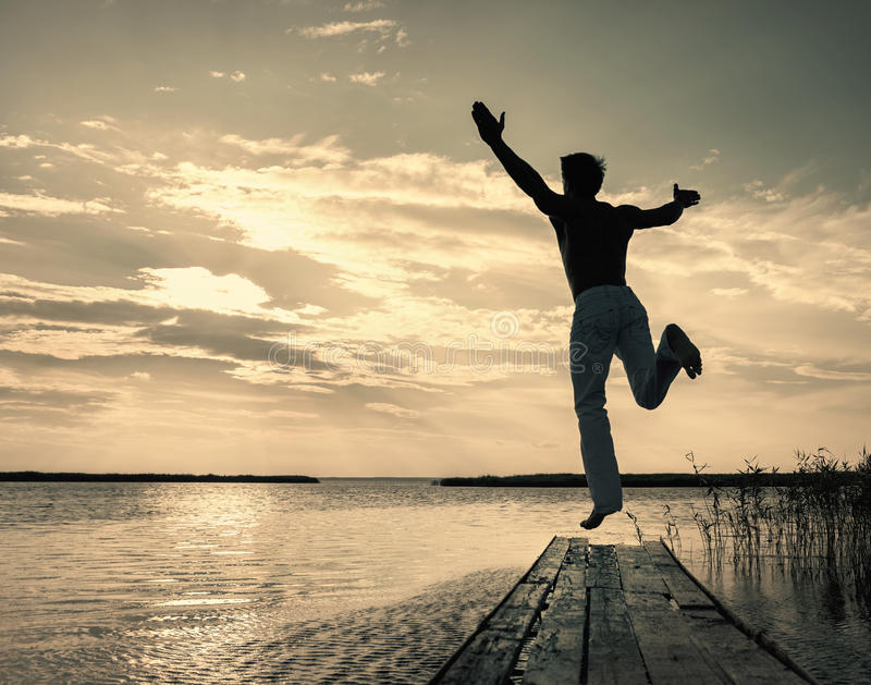Man jumping up off small jetty at sunset. Silhouette of man jumping up off small jetty at sunset royalty free stock photos