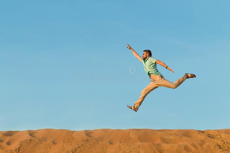 Man jumps over crests of dunes in the desert under the heated sun high. The right hand is hig stock images