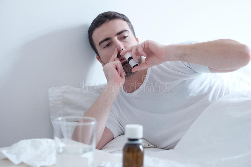 Man känslig förkylning och att använda en nasal sprej som ligger i sängen arkivfoto