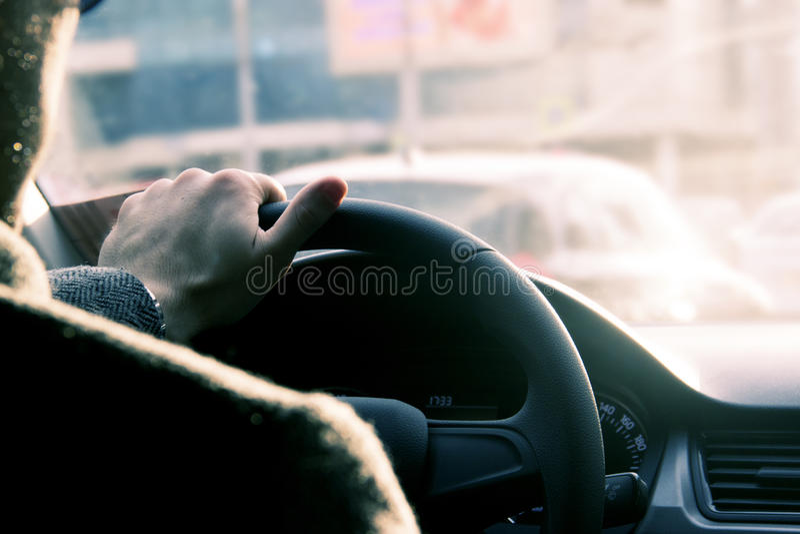 Man körning av bilen, hand på styrninghjulet som ser vägen framåt Körning av säkerhet i staden arkivfoto