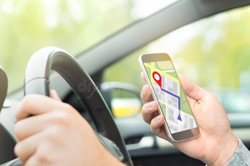 Man körning av bilen och att använda online-översikten och GPS applikationen arkivbilder