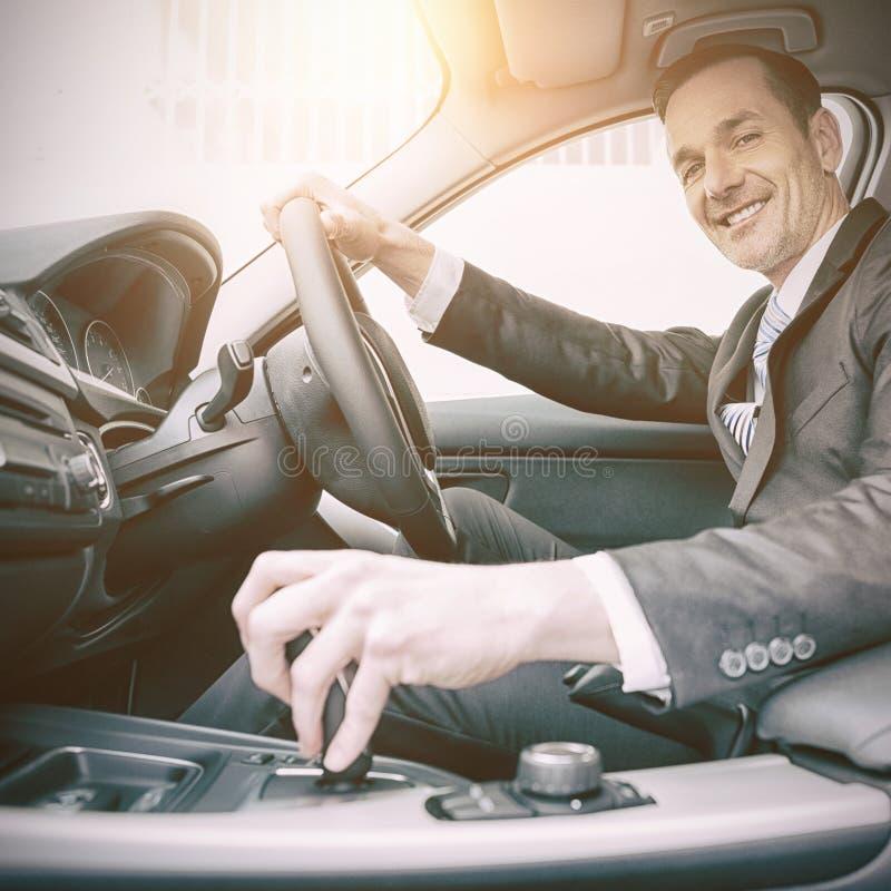 Man körning av en bil och att le på kameran royaltyfria foton