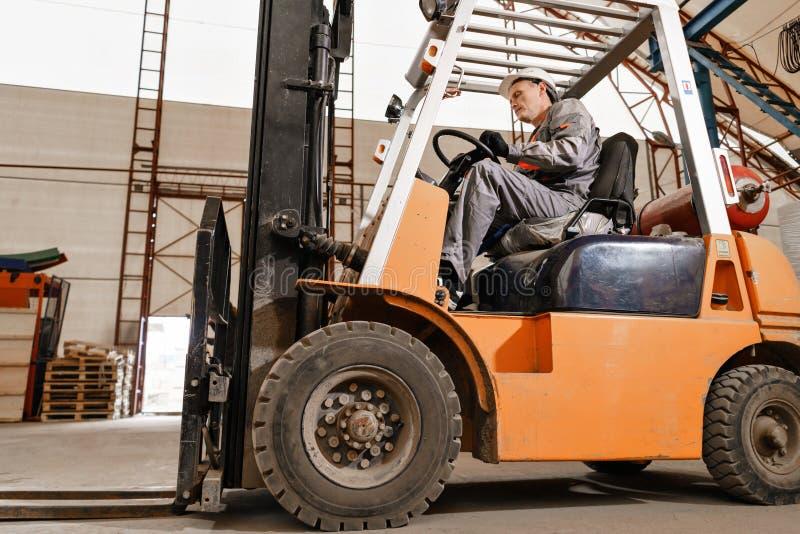 Man körning av en gaffeltruck till och med ett lager i en fabrik chaufför i enhetlig och skyddande hjälm Begreppet av royaltyfria bilder