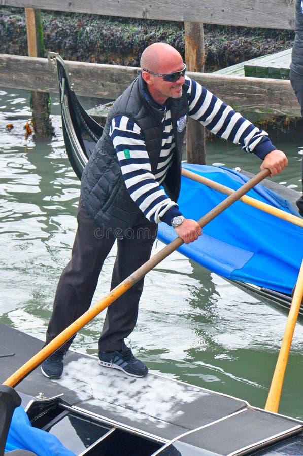 Man körning av gondolfartyget i Venedig, Italien royaltyfri bild