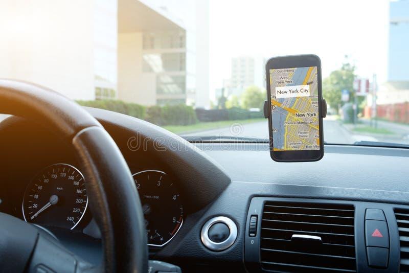 Man körning av hans bil genom att använda hans mobilgps arkivfoto