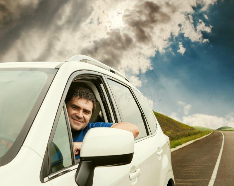 Man körning av hans bil på den ensamma vägen fotografering för bildbyråer