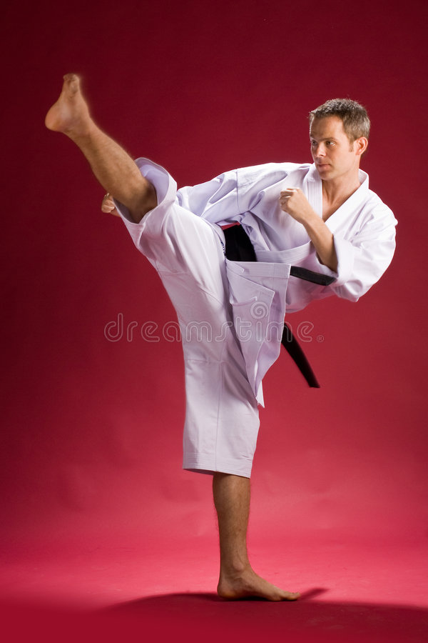 Man karate kicking. A studio view of a man in a white kimono with his leg high in the air in a classic karate kicking pose. Red background stock photo