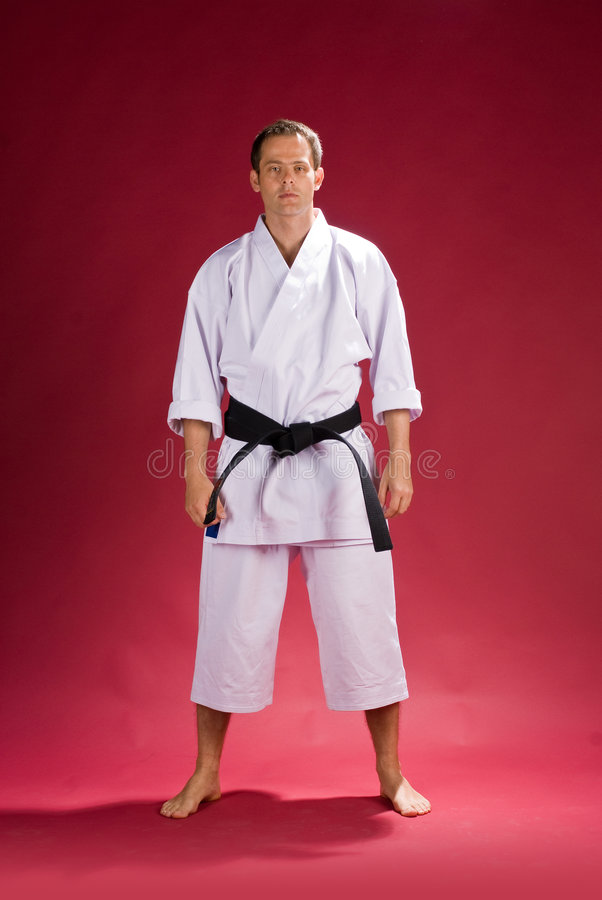 Man in karate kimono. With black obi belt and red background royalty free stock photos