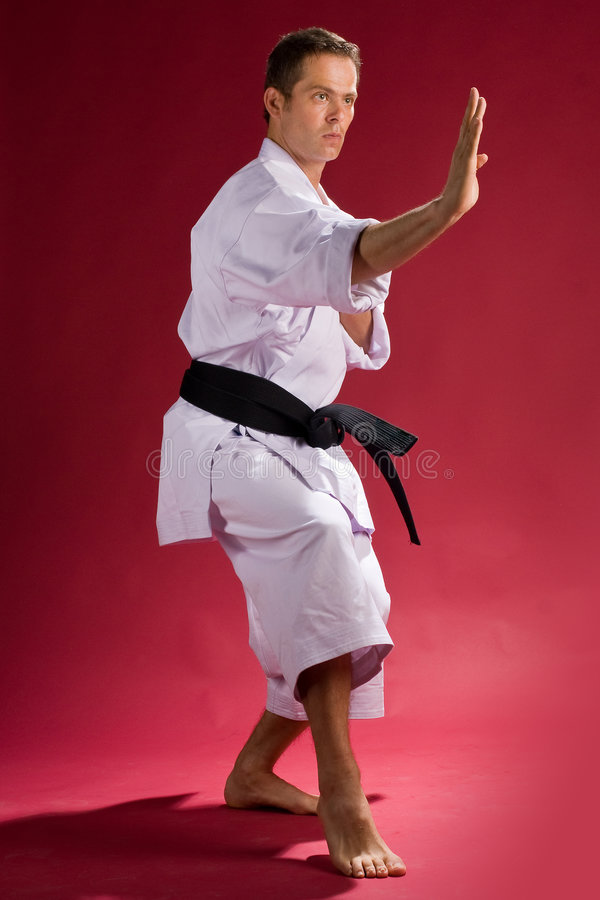 Man in karate pose. A view of a young man wearing a white kimono and black belt, standing in a karate pose. Red background royalty free stock photos