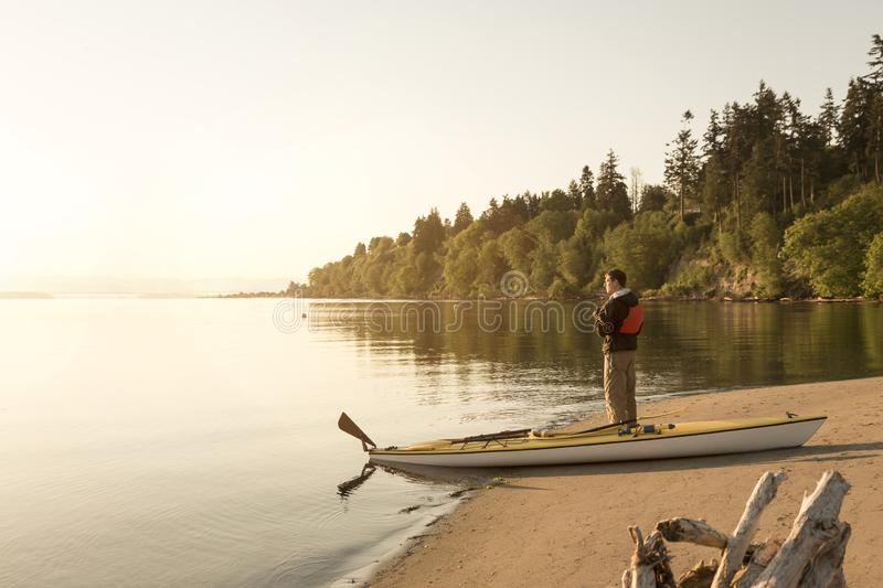 Man with kayak on beach looking out at water. Solo outdoor adventure sports sea kayaking in beautiful, remote nature wilderness stock images