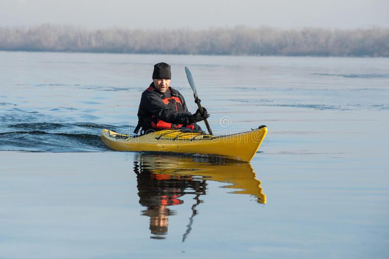Man with the kayak. Journey in the winter and spring of the water stock images
