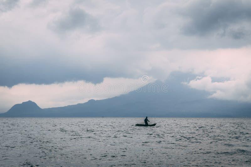 Man on kayak on lake in front of mountain stock image