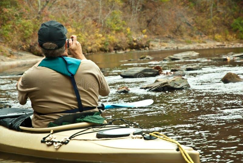 Man in Kayak Taking Pictures stock photo