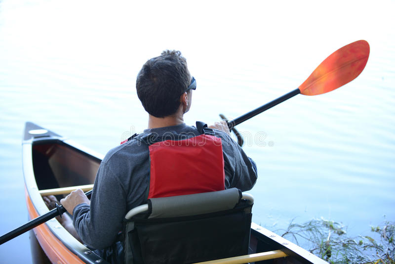 Man in kayak wearing sunglasses looking off into distance. On lake stock photos