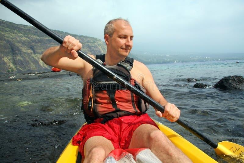 Man kayaking. Mature man kayaking in the ocean on Big Island, Hawaii royalty free stock photography