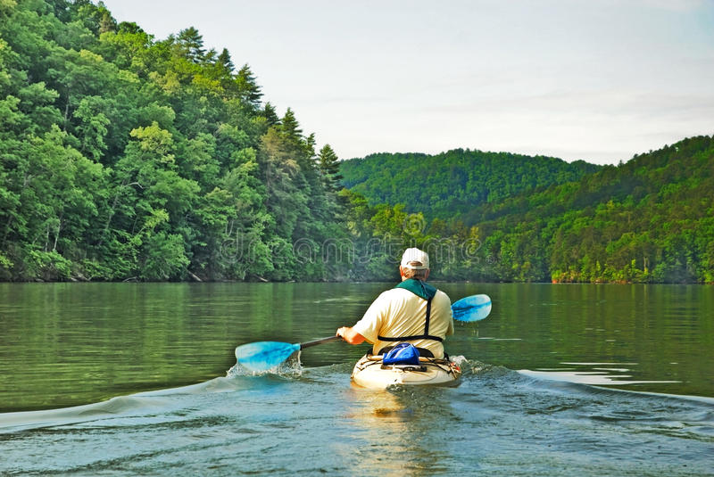 Man Kayaking on Quiet Lake. An older man out for a peaceful kayaking trip on a pretty mountain lake. He has on an inflatable life vest royalty free stock photos