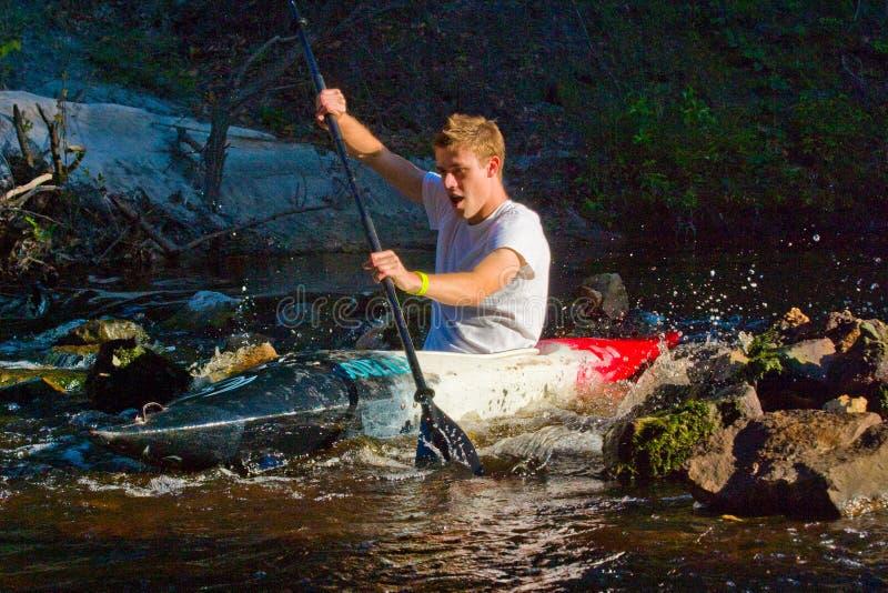 Man kayaking on river. A young man kayaking on swift river royalty free stock image