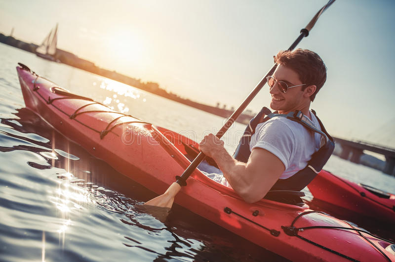 Man kayaking on sunset. Handsome sporty man is kayaking on sunset. Canoeing alone royalty free stock photos