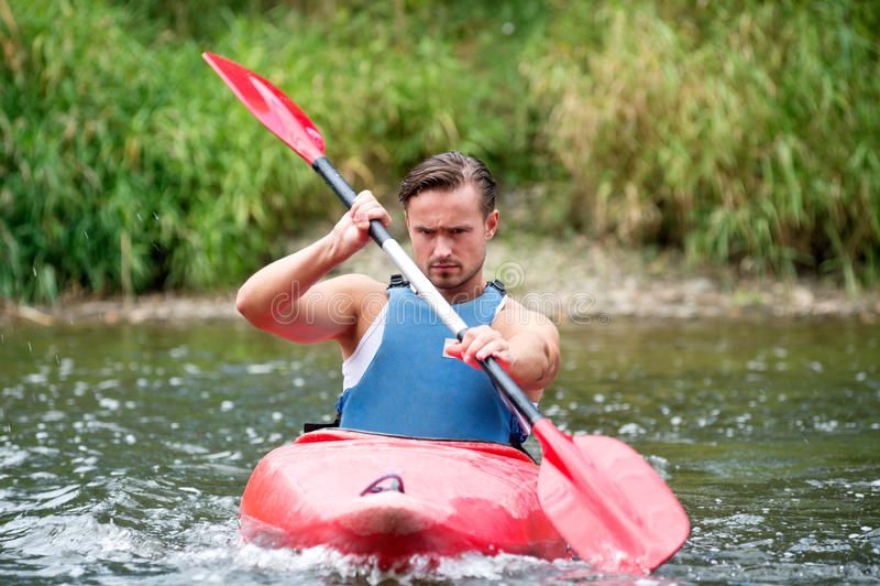 Man kayaking. A young man kayaking down a river royalty free stock photo