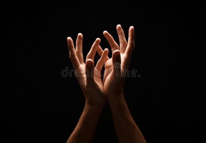 Man keeping hands in cupped shape, cutout on black. Outstretched male hands, man keeping empty cupped palms together isolated on studio black background stock image