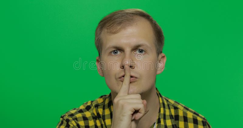 Man keeping a secret or asking for silence, serious face, obedience concept. Handsome young man in the yellow shirt keeping a secret or asking for silence stock image