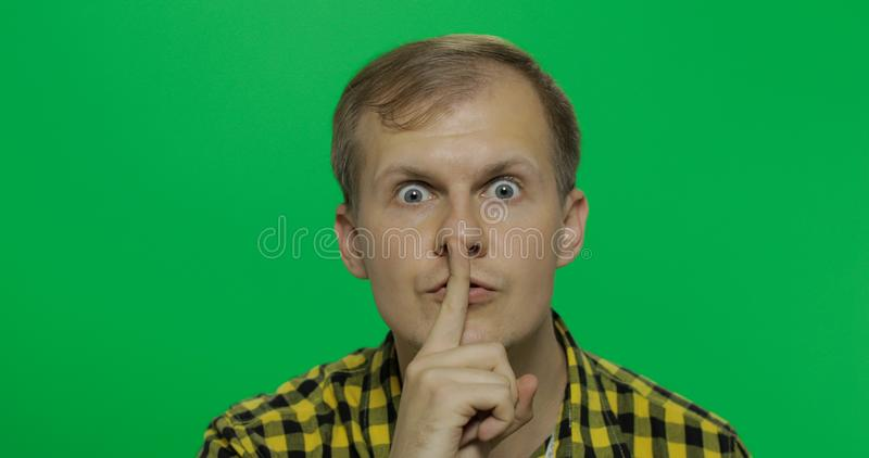 Man keeping a secret or asking for silence, serious face, obedience concept. Handsome young man in the yellow shirt keeping a secret or asking for silence royalty free stock image