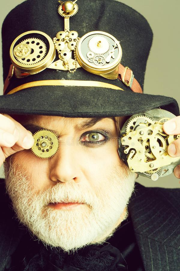 Man keeps cogwheel and gears. Senior bearded man or watchmaker with white beard in black hat keeps cogwheel and mechanical metallic gears on grey wall royalty free stock image