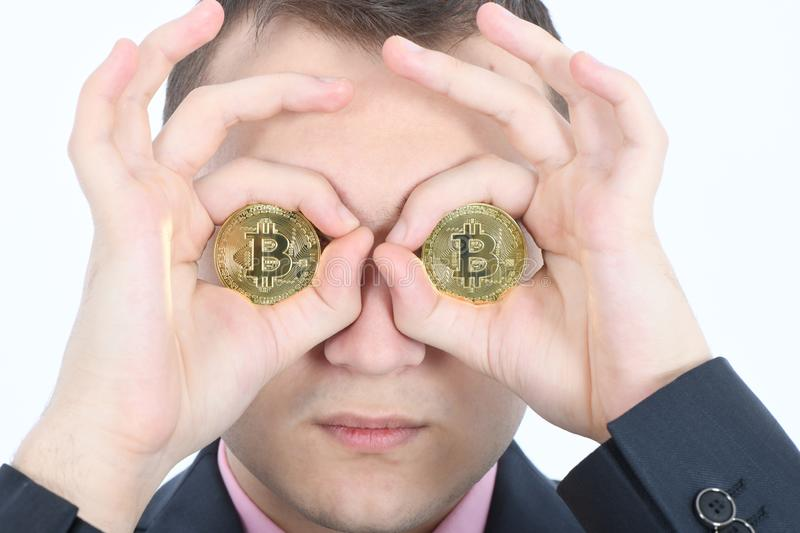 Man keeps the eye instead two golden cryptocurrency bitcoin in hands stock photo
