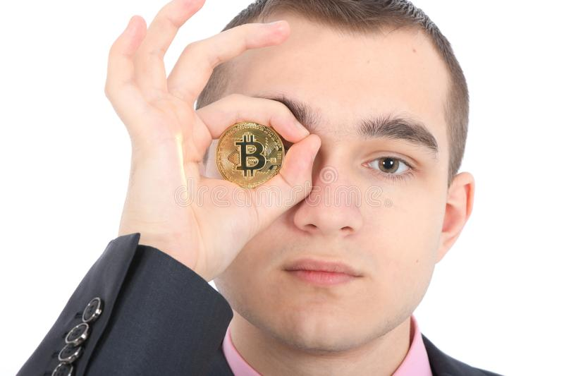 Man keeps the eye instead two golden cryptocurrency bitcoin in hands stock image
