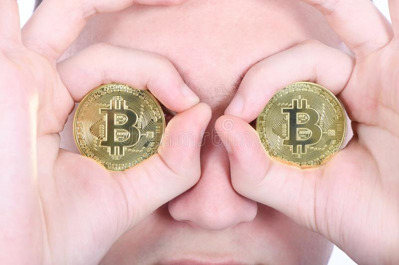 Man keeps the eye instead two golden cryptocurrency bitcoin in hands stock photos