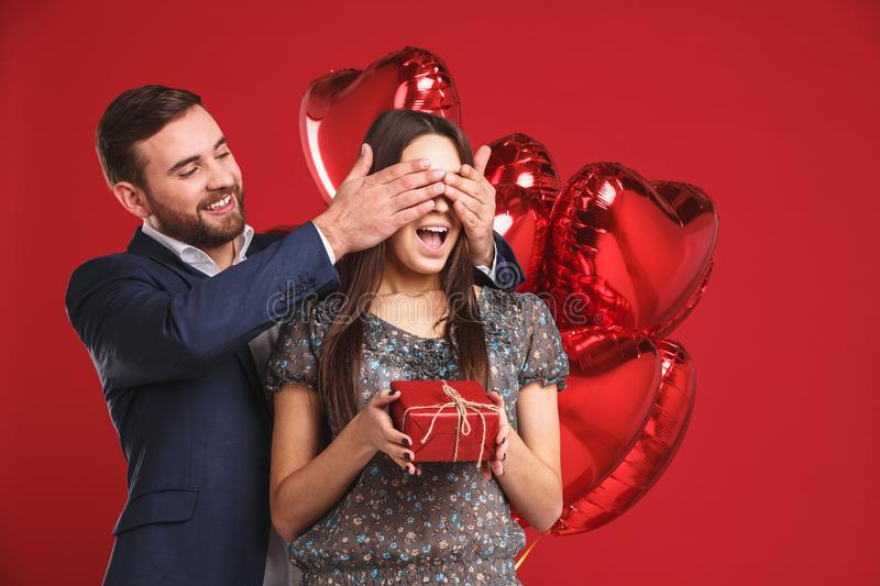 Man keeps his girlfriend eyes covered while she giving a gift , romantic surprise for Valentines day stock photos