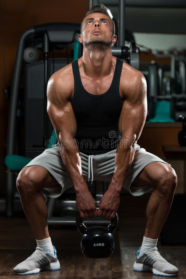 Man And Kettle Bell. Muscular Man Exercise With Kettle Bell stock photos