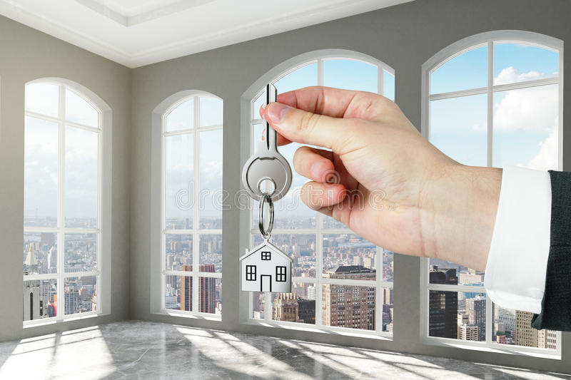 Man with key in hand in modern empty room with concrete floor royalty free stock image