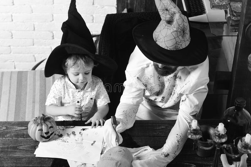 Man and kid with busy faces in witch hats draw and decorate pumpkins. Halloween and holiday concept. Man and boy in room royalty free stock images