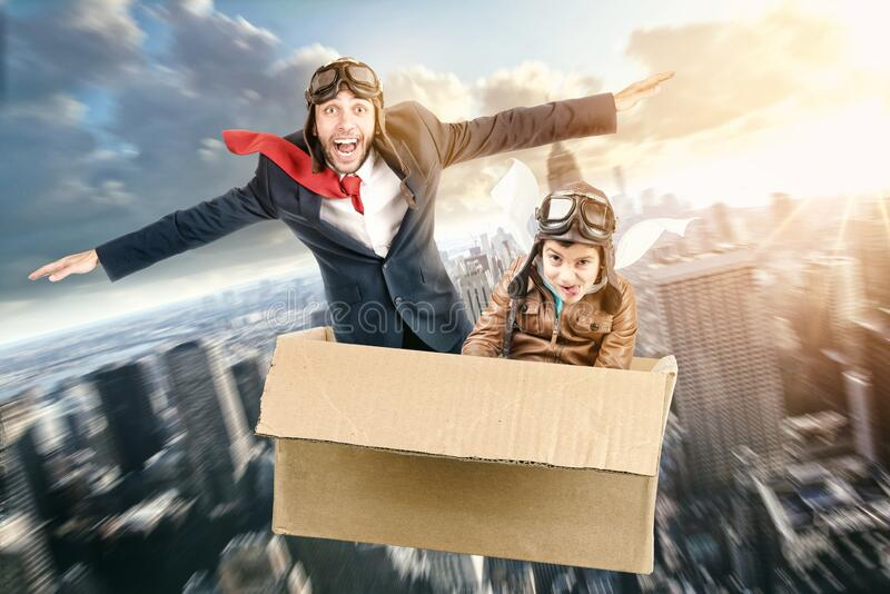 Father and son flying in a cardboard box stock photo