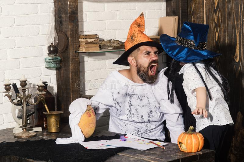 Man and kid with mad faces in witch hats. Play with pumpkins. Witcher and little magician make Halloween decor. Halloween and party concept. Man and boy on royalty free stock images