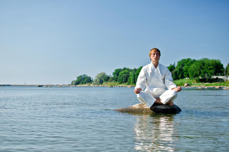 Man in kimono meditating. On the rock in the sea stock images
