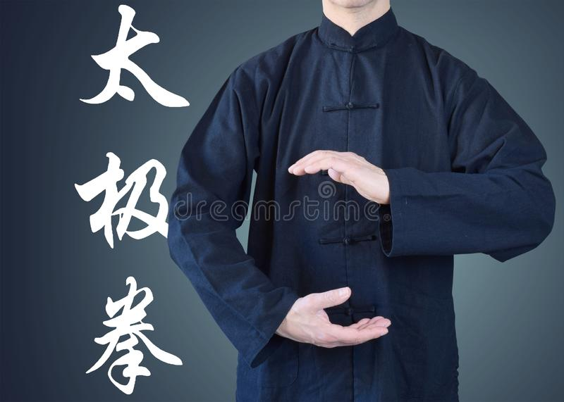 Man in kimono, in a position of tai chi stock photography