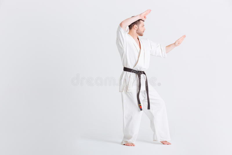 Man in kimono preparing for fighting. Isolated on a white background stock image